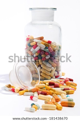 Variety of pharmaceutical capsules and pills lying on a white surface with an open half filled glass jar behind in a health care concept - stock photo