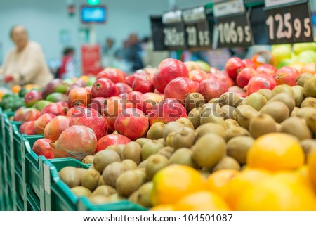 Variety of pomegranate fruits and kiwi fruits in boxes in supermarket