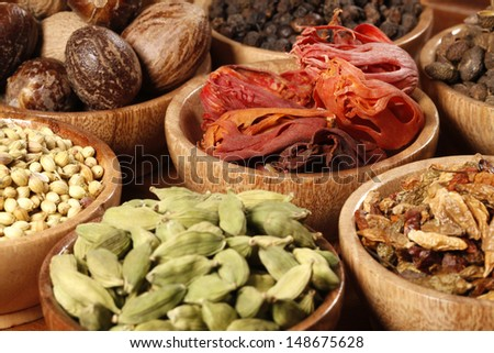 Variety of raw Authentic Indian Spices on wooden bowl. - stock photo