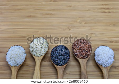 Variety of rice in wood spoon on wood background. From left: Japanese rice, pounded brown rice, forbidden rice (rice-berry), pounded red rice, jasmine rice - stock photo