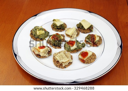 Variety of round multi grain cracker appetizers topped with basil pesto or horseradish, cheese pieces, ground black pepper, and hot sauce on half of them. A round, white dish of simple, healthy snacks - stock photo
