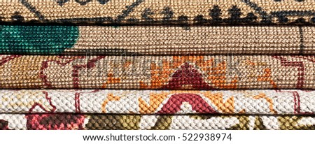 Variety of samples of bright, colorful carpet fabric in oriental style for a decoration, needlework and  interior purposes. A street bazaar in flea market. Israel