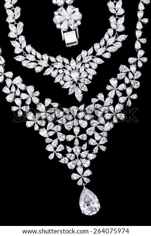 Variety of silver jewellery items on black background - stock photo
