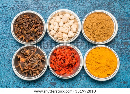 Variety of spices and herbs in a cup  on a wooden background.