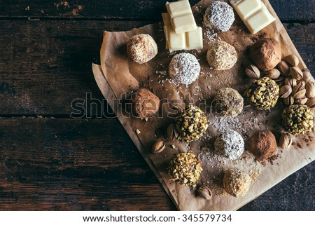 Variety of sweet homemade chocolate pralines on wooden background  - stock photo