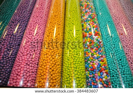 Variety of sweets and candies in a transparent plastic tubes full of thousands of colorful candies