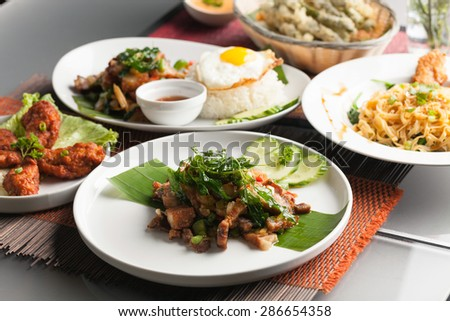 Variety of Thai food and stir fry dishes.  Shallow depth of field. - stock photo