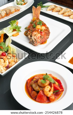 Variety of Thai style whole fish red snapper sweet and sour shrimp gyoza dumplings sesame breads seafood salad and other spicy Thai dishes. - stock photo
