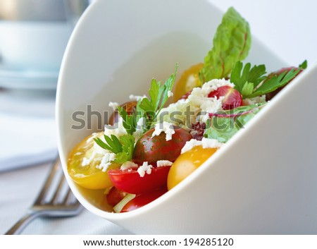 Variety of Tomato salad in a white bowl with ricotta cheese in a restaurant