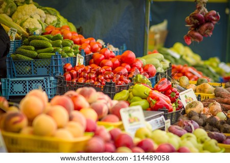 Variety of tomatoes, peppers, peaches, onions, beet roots, carrots and other on city market - stock photo