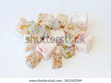 Variety of Turkish Delight with pistachios, walnut, figs and rose and powdered sugar and coconut - stock photo