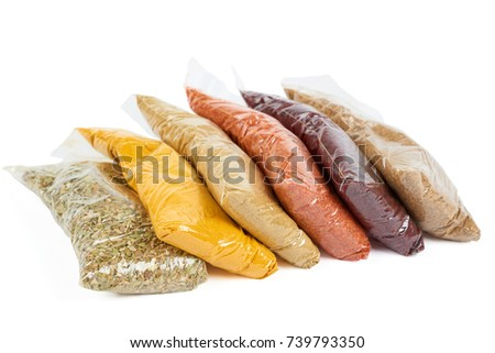 Variety of turkish spices in transparent package over white. From left to right: oregano, indian saffron, cumin, chilly, spice for salad, coriander