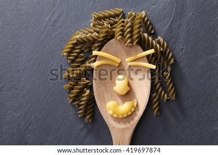 Variety of types and shapes of Italian pasta form human face - stock photo