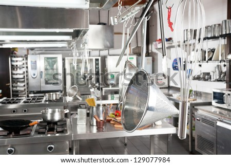 Variety of utensils hanging in commercial kitchen - stock photo