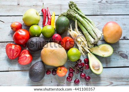 Variety of vegetables and fruits on rustic background, top view, horizontal border. Vegan food or diet eating concept.