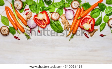 variety of vegetables ingredients for healthy eating and cooking on white wooden background, top view, border. Vegetarian or diet food concept. - stock photo