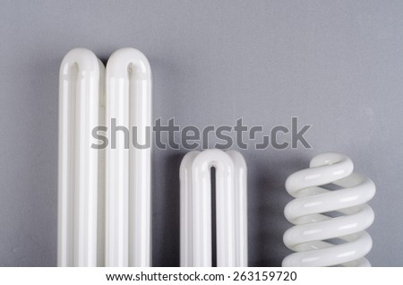 variety of white energy saving bulb on grey background - stock photo