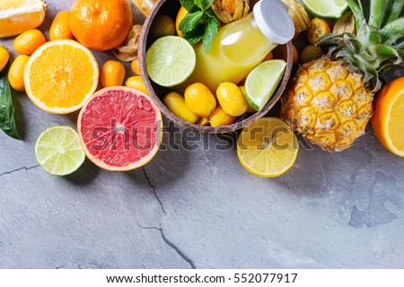 Variety of whole and sliced citrus fruits pineapple, grapefruit, lemon, lime, kumquat, clementine and physalis with mint, bottle of juice in bowl over gray textured background. Top view with space.
