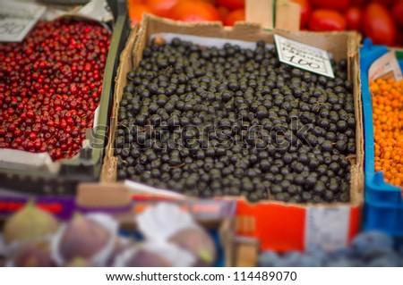 Variety of wild berries on table on city market - stock photo