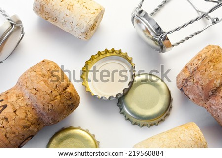Variety of wine bottle corks and beer bottle caps lying on white table surface after wild party with alcohol beverages - stock photo