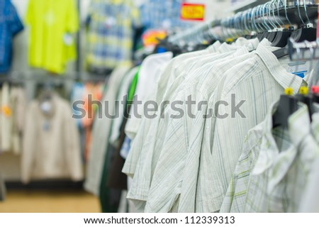 Variety os t-shirts on stands in supermarket