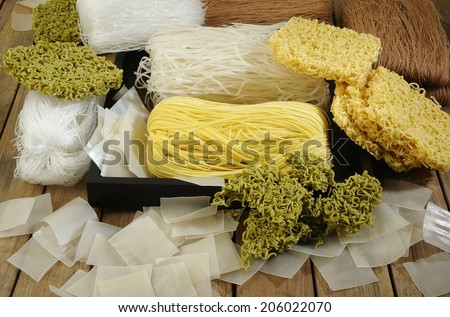 variety types and shapes of noodles on wooden background - stock photo