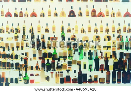 Various alcohol bottles in a bar, back light, all logos removed, toned - stock photo
