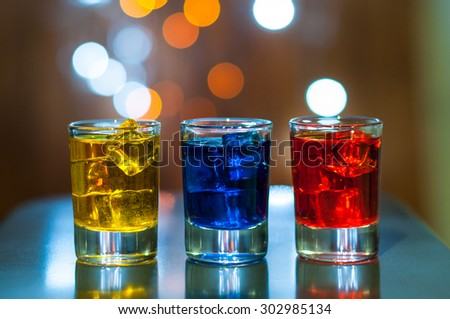 Various alcoholic cocktails on a bar counter with magic light bokeh background.