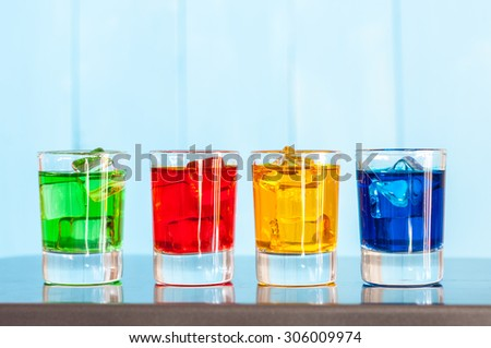 Various alcoholic cocktails on a bar counter with wooden background. - stock photo