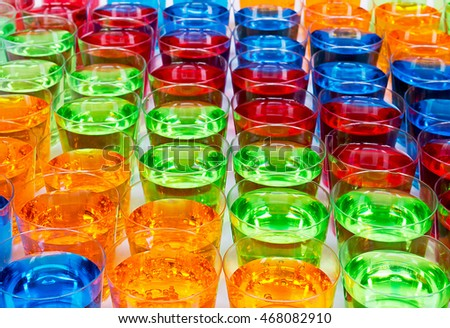 Various alcoholic shots in shot glasses creating multi colored drinks industry background