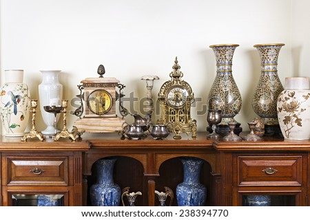 Various antique clocks vases and candlesticks on display - stock photo