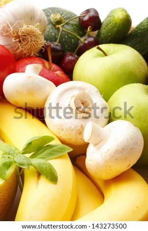 Various, assorted fruits and vegetables( apple, mushrooms, tomato, cherry, garlic, pumpkin, basil, cucumber, banana, green apple). Vibrant color.