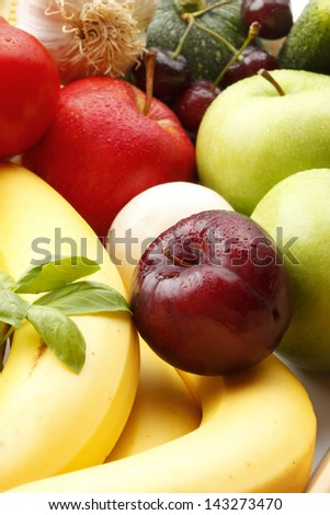 Various, assorted fruits and vegetables( Plum, banana, basil, apple, garlic, mushrooms, tomato, cherry, green apple). Vibrant color. - stock photo