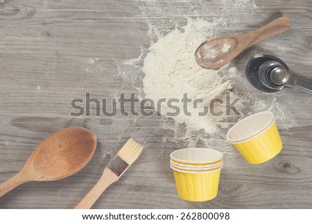 Various baking tools from overhead view on wooden table in vintage tone, copy space on top. - stock photo