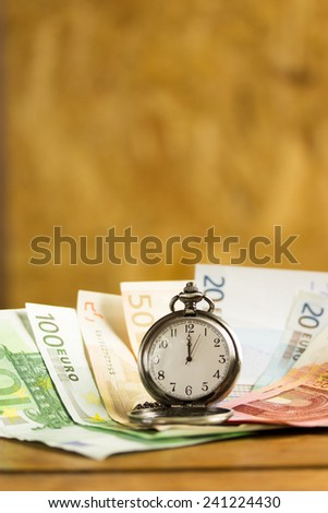 various banknotes and a pocket watch  - stock photo