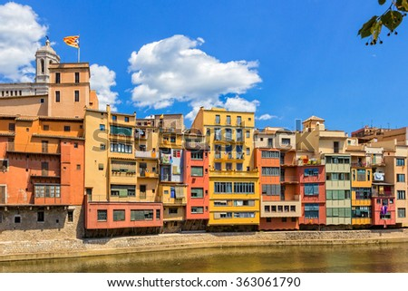 Various beautiful little houses over the edge of the Onyar river in Spain during the summer with blue sky