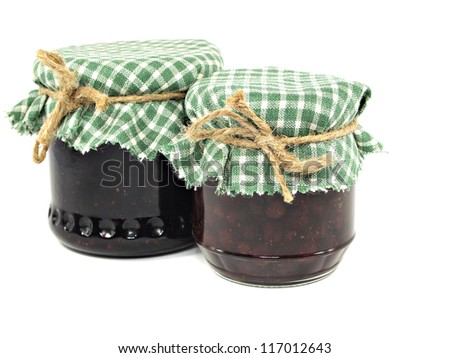 various berries and fruits jam in glass jar on white background