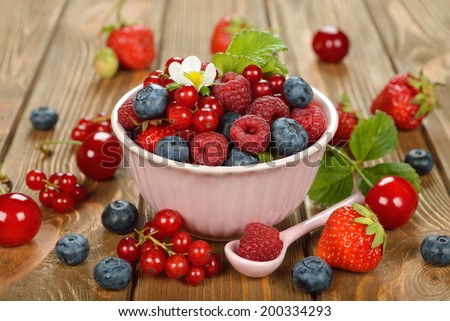 Various berries in a bowl on a brown background