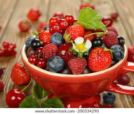 Various berries in a red bowl on a brown background