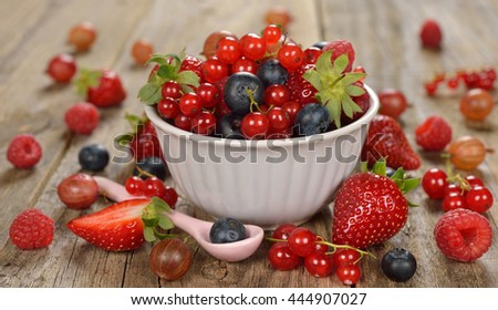 Various berries in bowl on a brown background