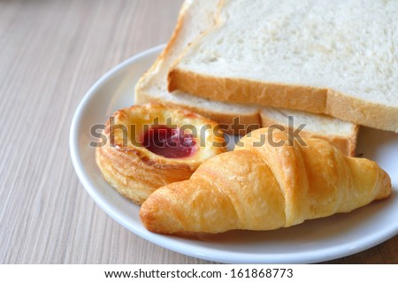 Various breads and Croissants on breakfast table.