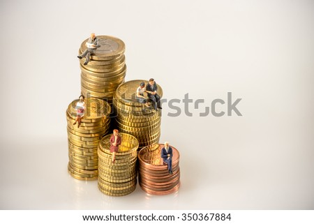 Various businesspeople sitting on money coin piles. Macro photo - stock photo