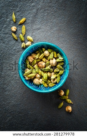 Various Cardamom Spices in Authentic Turkish Crockery. Dark Stone Background. Top view. Close up. - stock photo