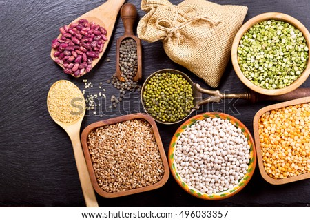 various cereals, seeds, beans and grains on dark background