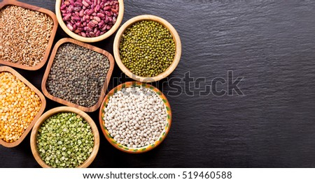 various cereals, seeds, beans and grains on dark background, top view with copy space