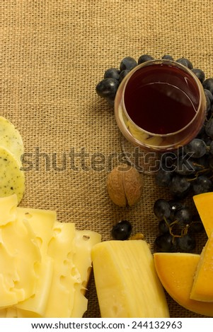 various cheese and red wine over a canvas background