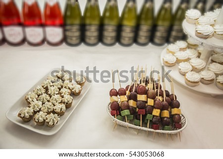 Various cheese banquet snacks on banquet table, catering event.  Colorful cheese with grape on wooden sticks. Various snacks on full boarded banquet table. Champagne or vine in bottles.