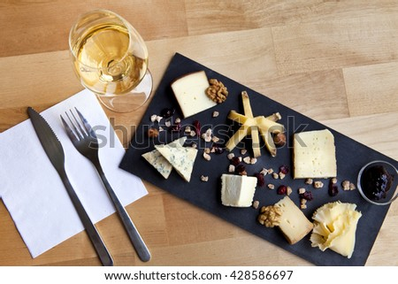 Various cheese on a slate plate and glass of white wine in a French bistro