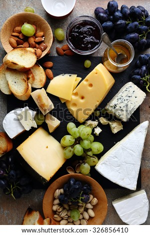 various cheeses and grapes on slate