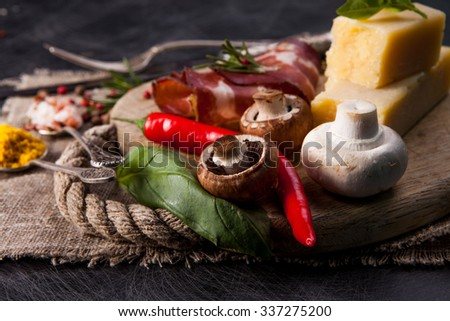 Various cheeses, salami and mushrooms on the wooden board - stock photo